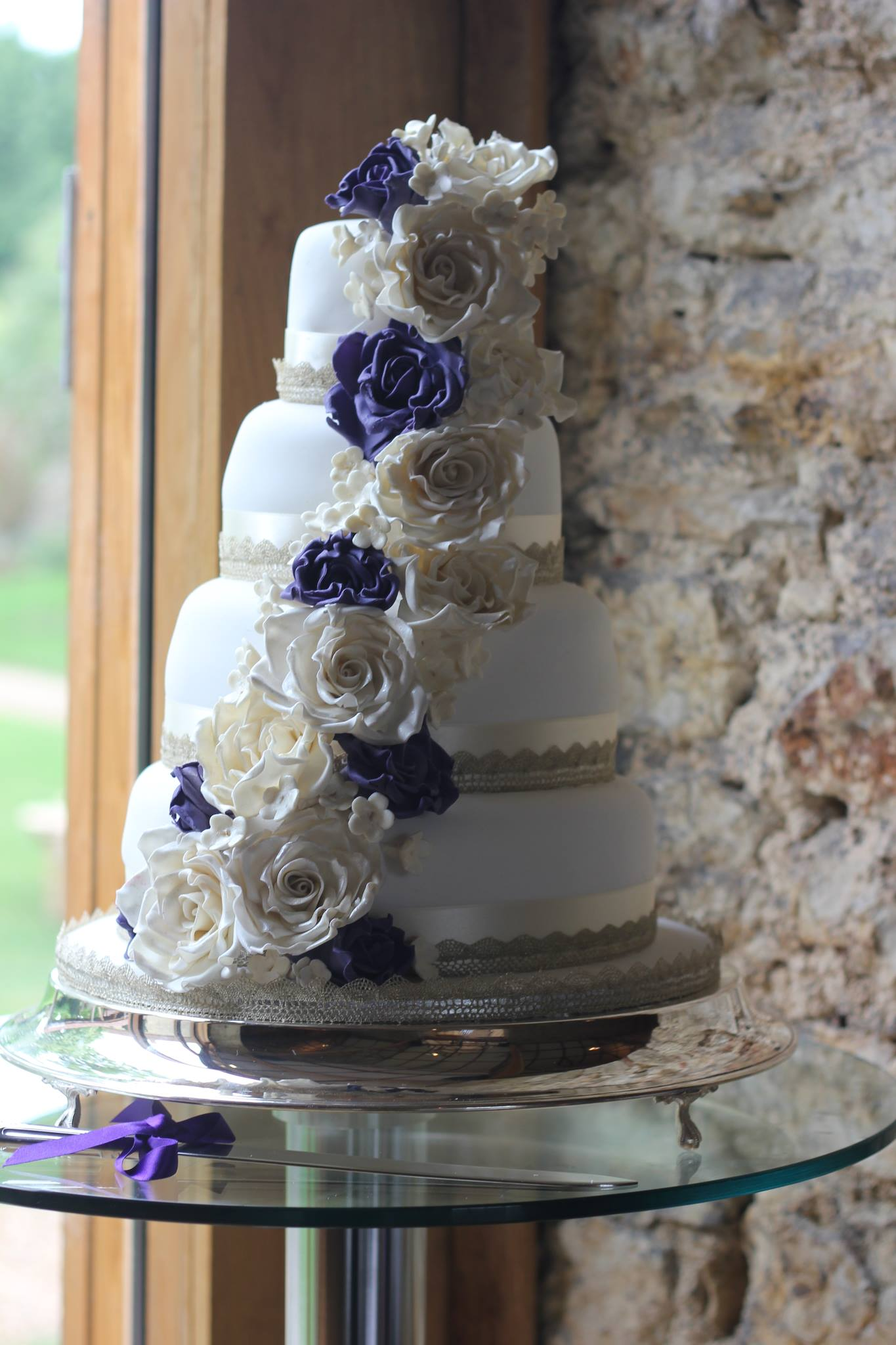 purple and white cascading flower 4 tier wedding cake