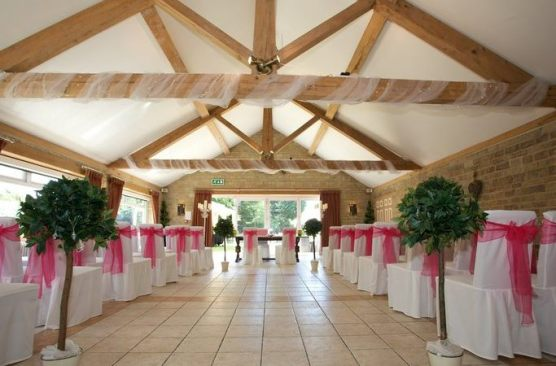Wedding Ceremony Set Up with Pink chair sashes and bay trees